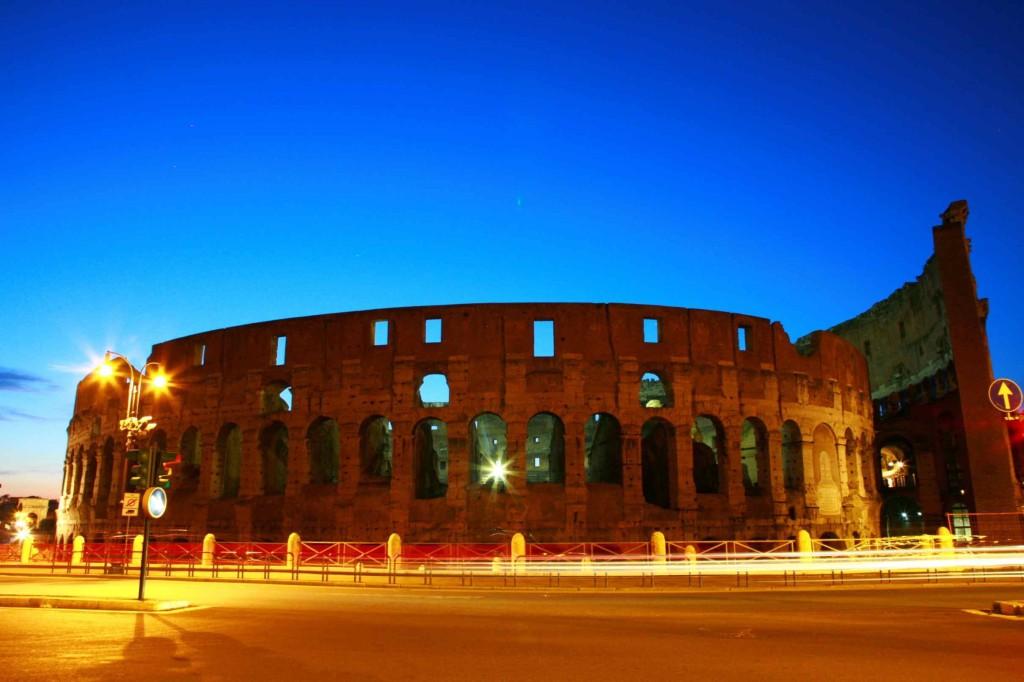 空が青く、ライトアップされたコロッセオ